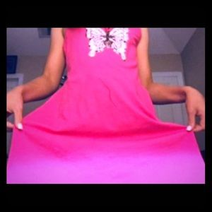 This is a pink dress with a butterfly in the midd.